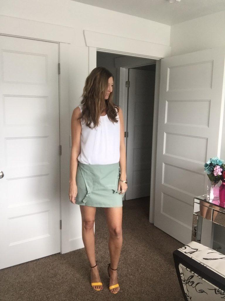 white sleeveless blouse and green jumper
