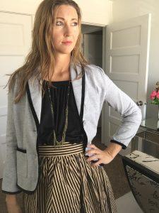 gray blazer, black top, and striped skirt